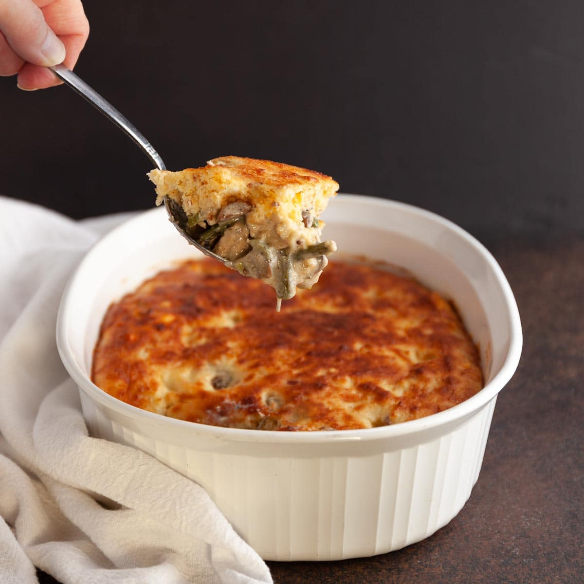 A serving spoon scooping out a square of chicken pot pie.