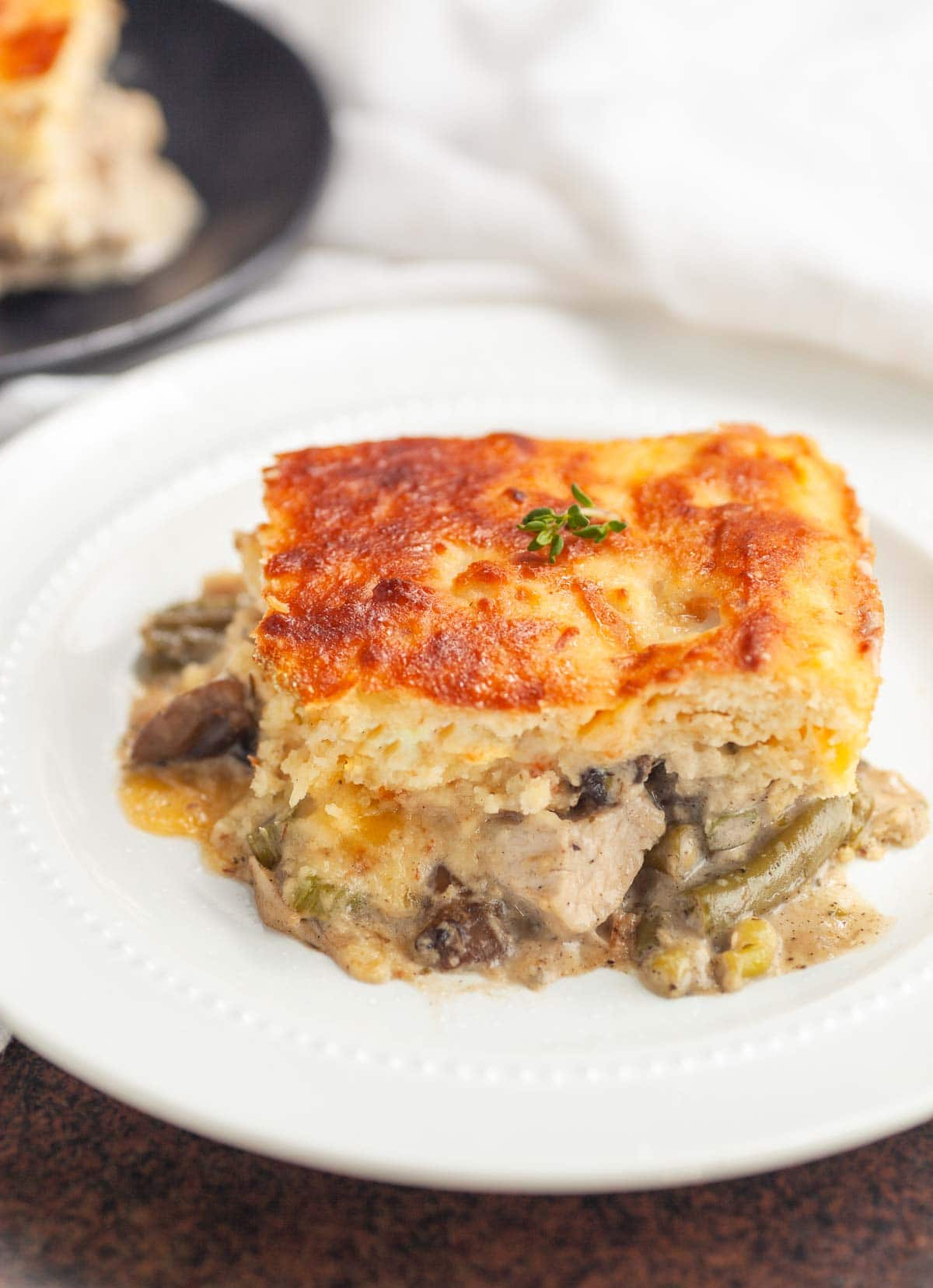 A slice of a chicken pot pie with a bacon biscuit crust.