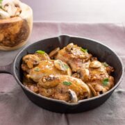 A cast iron pan with chicken mushroom an garlic in a yummy sauce.