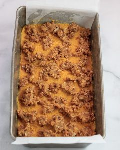 Sprinklwe crumble onto pumpkin loaf