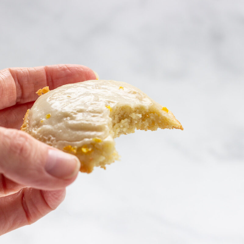 A keto lemon cookie with a bite taken out of it.