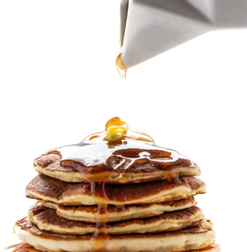 A keto pancake stack with a drop of syrup coming down on them.