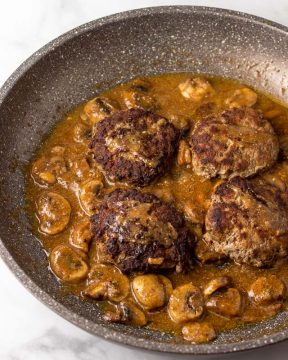 Return meat patties to the pan with gravy.