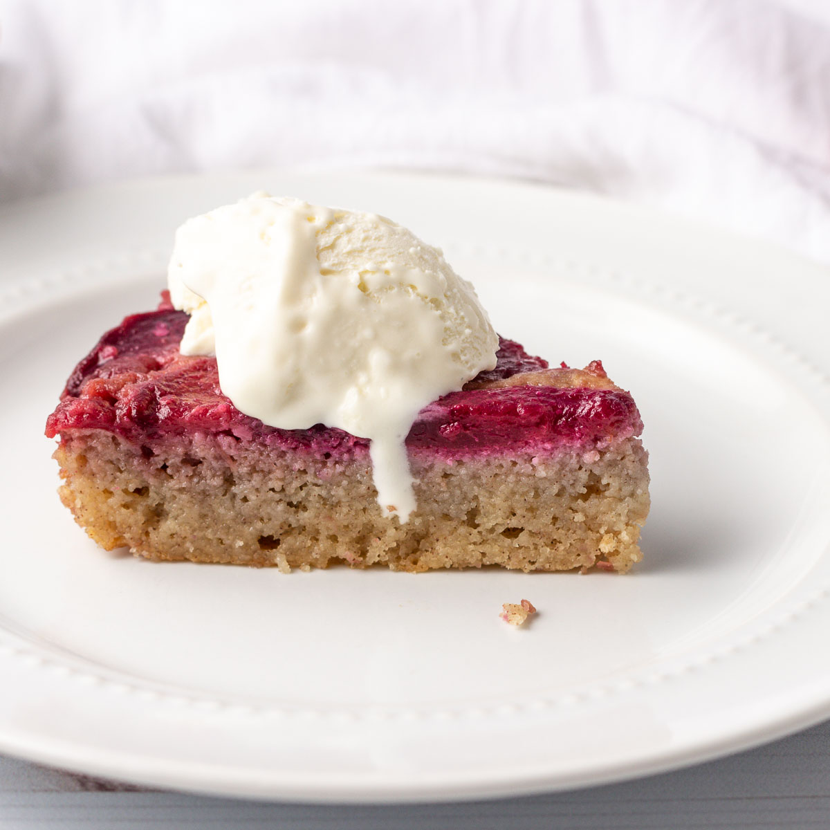 A slice of keto plum cake with low carb ice cream.