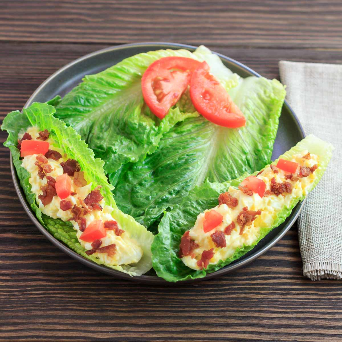 Egg salad bacon and tomato in 2 lettuce boats.