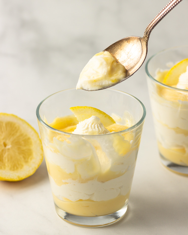 a spoonfull of a lemon cream parfait in a glass.