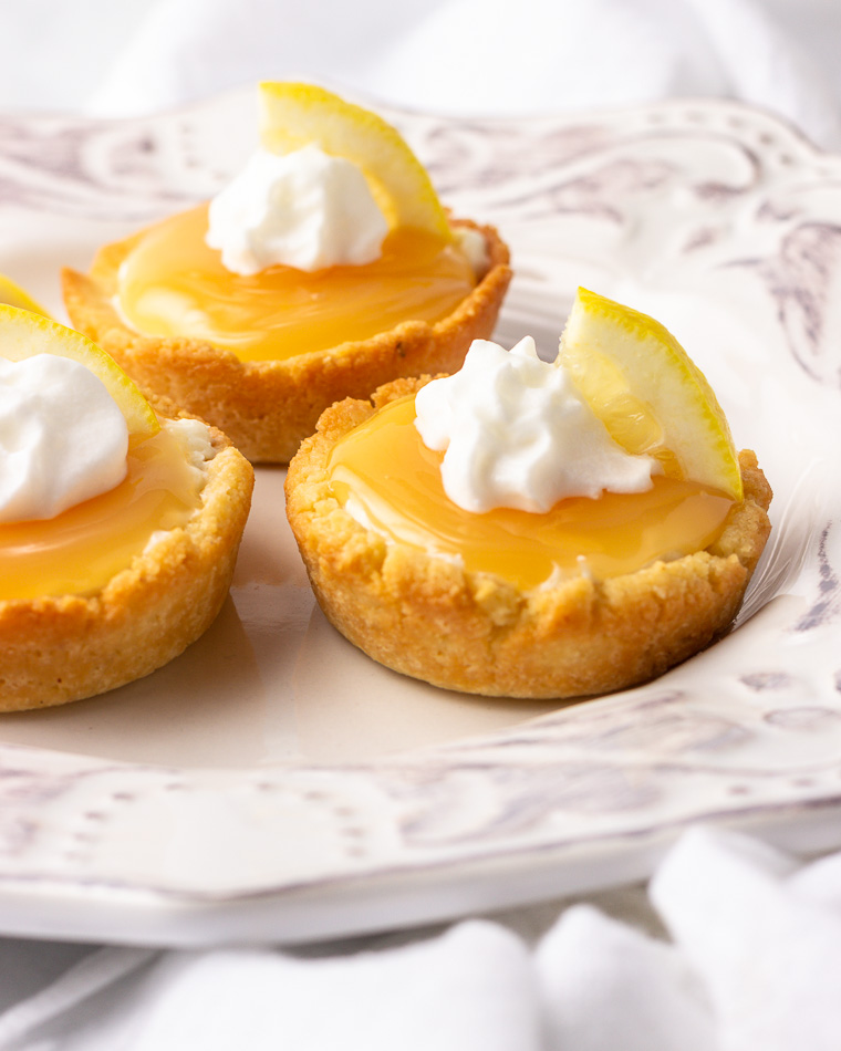 Three lemon supreme tarts with whipped cream.