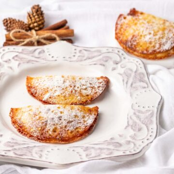 Two pumpkin turnovers with powdered sweetener.