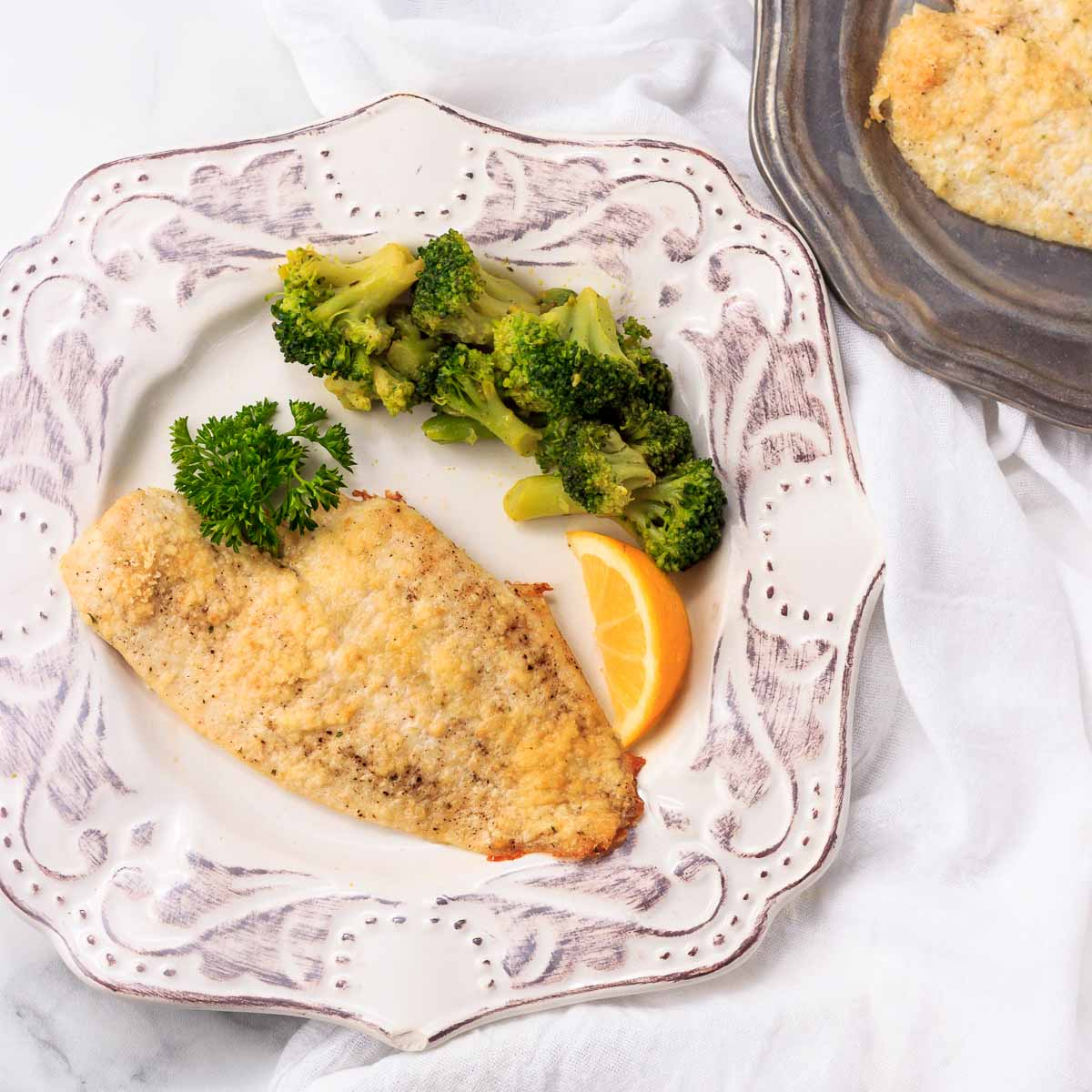 One low carb breaded and crusted fish fillet with broccoli.