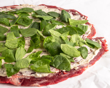 Layer spinach and filling on steak.