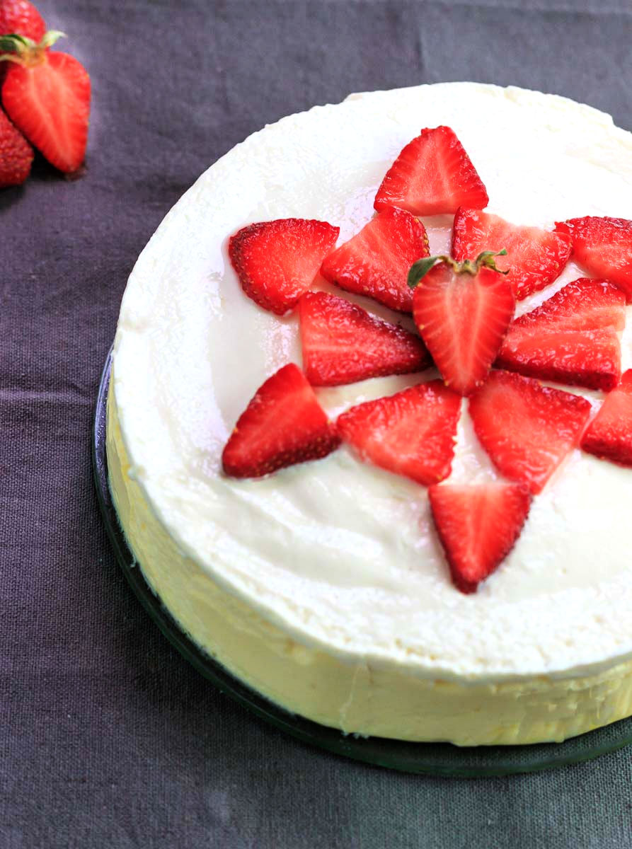 A whole keto cheesecake with sliced strawberries.