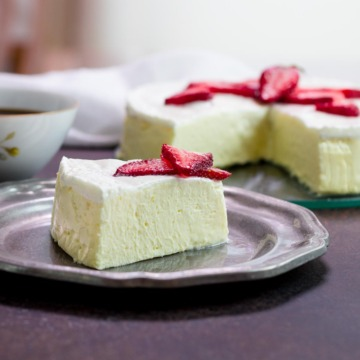 A slice of keto cheesecake with strawberries and a cup of coffee.