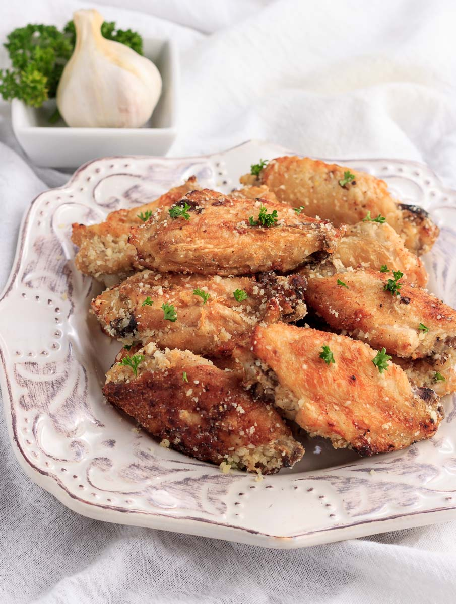 A stacked plate of chicken wingas with garlic & parmesan cheese.