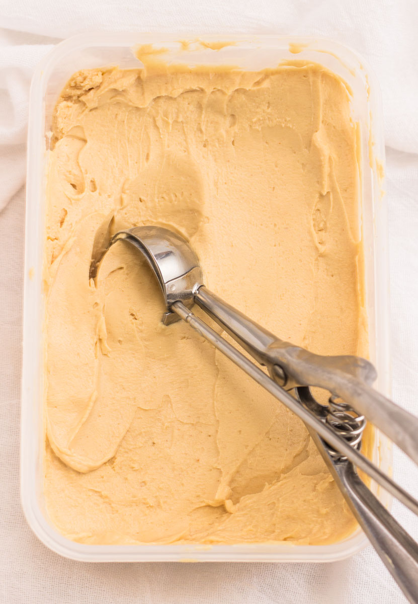 Scooping out a scoop of peanut butter frozen yogurt from a container.