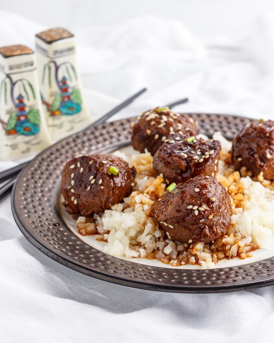Teriyaki meatballs with sauce over cauliflower rice.