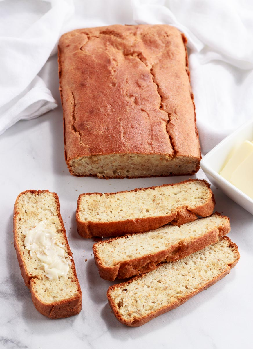 A keto crusty sliced loaf of bread with one slice buttered