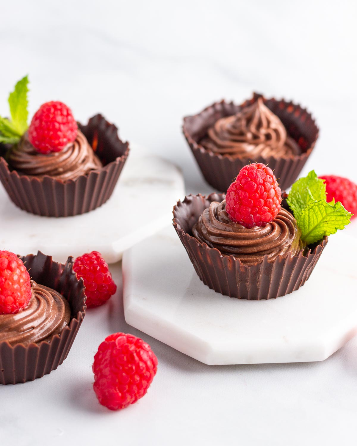 Four chocolaet cups filled with chocolate mousse and topped with a raspberry.