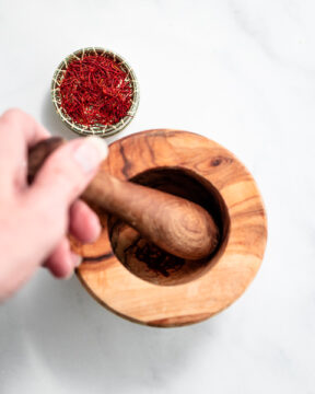 Grinding saffron threads into powder with a mortar and pestle.