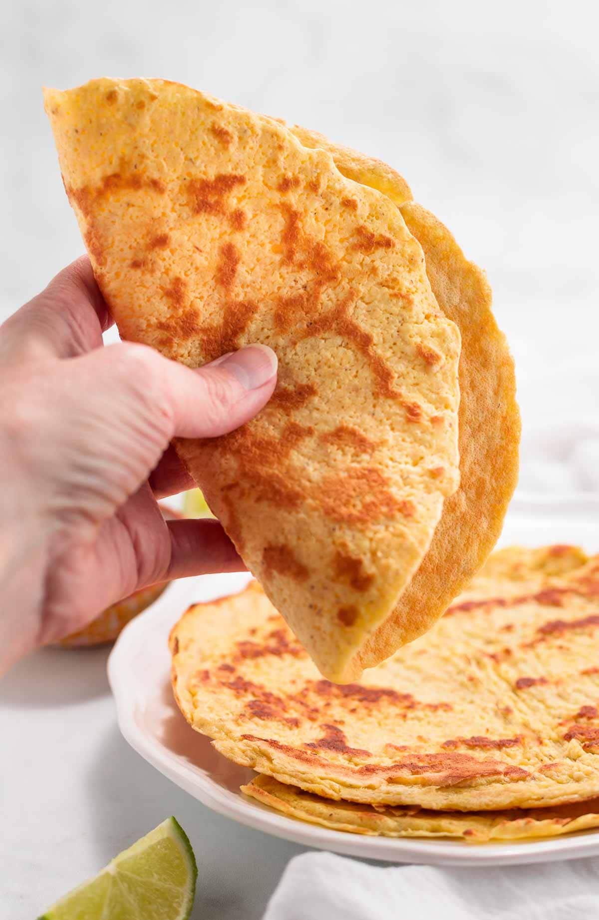A hand folding a keto tortilla in half.