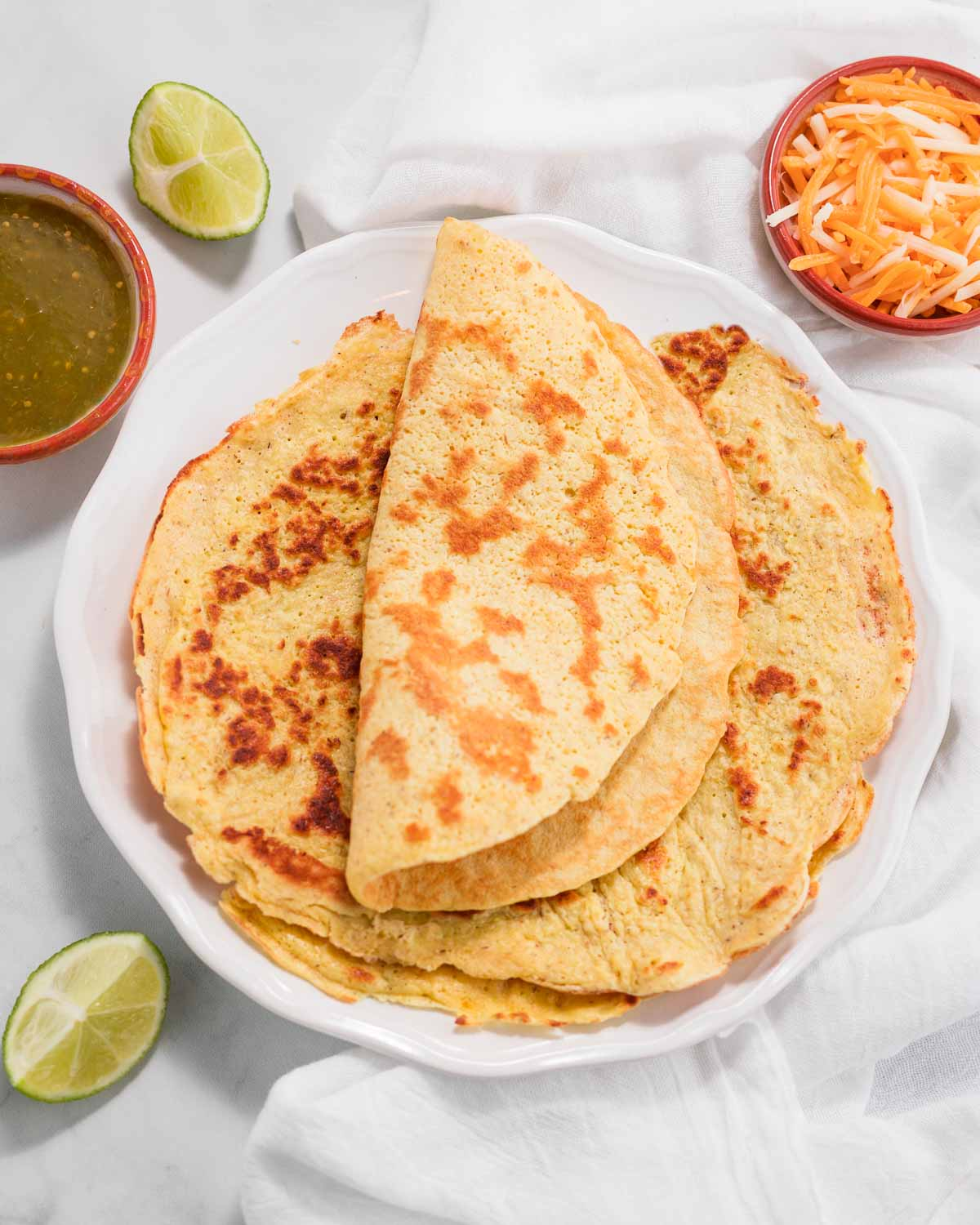 A stack of keto tortillas or wraps with one folded on top .