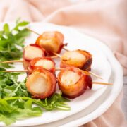 Bacon wrapped scallops on a bed of arugula