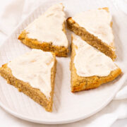 Four triangled shape pumpkin scones with icing.