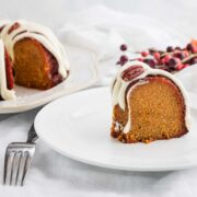 A slice of iced low carb pumpkin bundt cakke with the whole cake behind it.