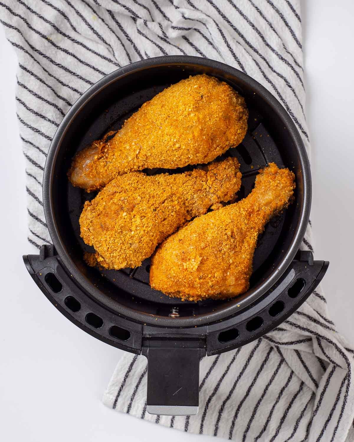 Placing the drumsticks into the air fryer.